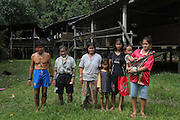2012: Penan native people; Baru (LHS), brother of Banai Tebai (2nd LHS) and Rasa (middle) and extended family, (On RHS) 17+yr old Senorita Along, daughter of Den Along Sega, with her son Dimas, 1yr old. They now living a settled but smi-hunter-gatherer lifestyle in Dayak hardwood  homes. Long Gita, Limbang District, Sarawak Borneo 2012<br /> <br /> Nomadic decades ago, have been forced to move up-river, to settled accomodation, far from their original hunter-gatherer grounds. The sound of chainsaws is not too distant, oil palm plantations are looming and the pipeline is right next door. Long Adang and Long Gita, Limbang Sarawak, Borneo..The huge Petronas Sabah-Sarawak pipeline is being built across the Borneo rainforest through native areas. Petronas is the government cash cow which funds about 45% of its budget. New roads are being built, though much of the transport follows the existing roads and infrastructure created by logging. Whilst the government heralds the project as a source of jobs for local people, it is unlikely to bring much but wanton damage to rainforest habitat and paving the way for further deforestation by oil palm plantations. Sarawak's primary rainforests have been systematically logged over decades, threatening the sustainable lifestyle of its indigenous peoples who relied on nomadic hunter-gathering and rotational slash & burn cultivation of small areas of forest to survive. For the natives this is disaster, a rapidly disappearing way of life, forced re-settlement, many becoming wage-slaves. Large and medium size tree trunks have been sawn down and dragged out by bulldozers, leaving destruction in their midst, and for the most part a primary rainforest ecosystem beyond repair. Nowadays palm oil plantations and hydro-electric dam projects cover hundreds of thousands of hectares of what was the world's oldest rainforest ecosystem which had some of the highest rates of flora and fauna endemism, species found there and nowhere else on Earth