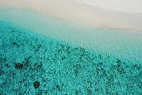 Aerial view of a man swimming on the shore of the beach with turquoise water in North Province, Maldives