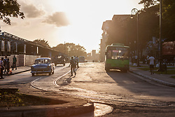 Pedestrian crossing road during sunset, Havana, Cuba