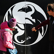 Steve and Emiko looking at a penguin graphic on a wall in Cape Town, South Africa