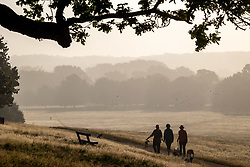Licensed to London News Pictures. 06/09/2021. London, UK. Walkers enjoy a warm misty start to the day in Richmond Park, south-west London as weather forecaster predict a mini-heatwave for September this week with temperatures hitting over 29c tomorrow. Photo credit: Alex Lentati/LNP