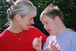 Mother with arm around teenage son with Downs Syndrome smiling,