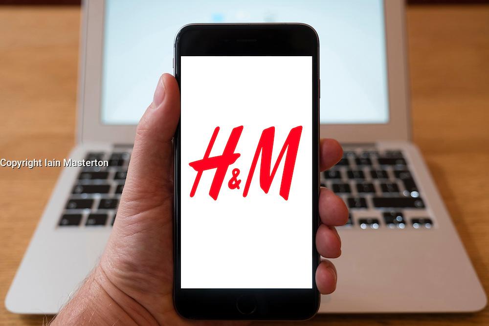 Using iPhone smartphone to display logo of H&M high street fashion retailer