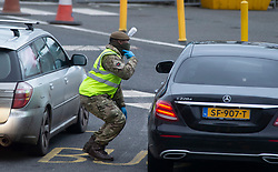 © Licensed to London News Pictures 26/12/2020.        Dover, UK. An army soldier helping to test people in Dover. Over 1000 lorries are left queuing on the M20 heading for Dover as Manston Airport is cleared. Emergency services and military personnel continue to tests travellers at Dover in Kent for Coronavirus before they cross the English Channel. Photo credit:Grant Falvey/LNP
