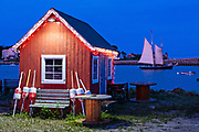 A Windjammer sailboat passes behind a red fish house into Wills Gut at twilight in Orrs Island, Maine.