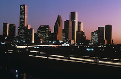 Sunset view of the Houston, Texas skyline from the northwestern side with motion blur of freeway traffic in foreground.