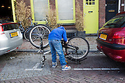 Een jongetje repareert zijn fiets.<br /> <br /> A boy is fixing his bike.