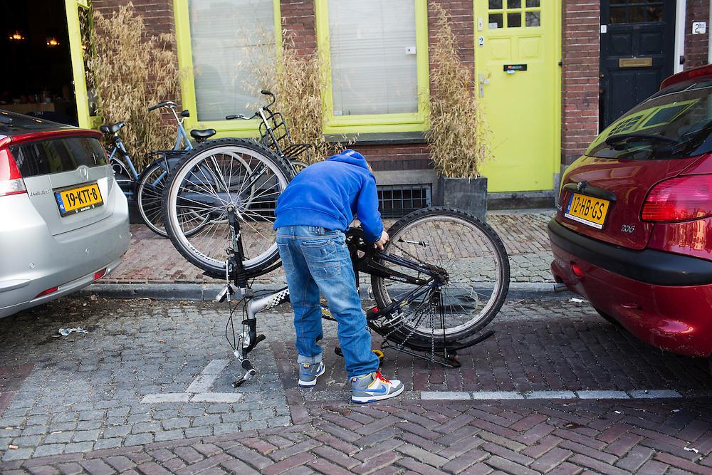 Een jongetje repareert zijn fiets.<br /> <br /> A boy is fixing his bike.