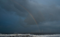 © Licensed to London News Pictures. 19/01/2014<br /> <br /> Teesside, England<br /> <br /> A rainbow forms over the offshore wind farm at the mouth of the Tees.<br /> <br /> Photo credit : Ian Forsyth/LNP
