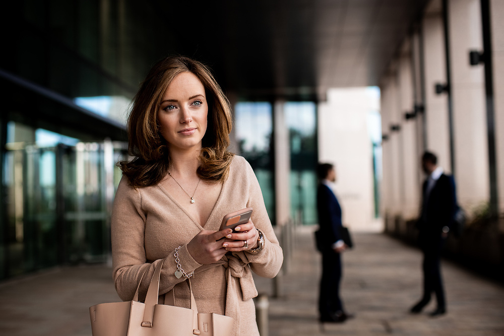 Business woman using her phone stood outside the Gaspe House corporate offices in the banking and finance district of St Helier Jersey, CI
