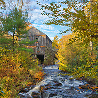 The saw mill at Moore State Park in Paxton, MA framed by beautiful New England fall foliage. This State Park is a peaceful retreat in the heart of central Massachusetts. This photo was taken on a beautiful autumn late afternoon when New England fall color was at peak and the sky featured a great mixture of blue sky and clouds.<br />