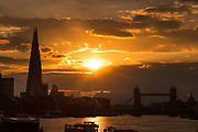 Sunset behind Tower Bridge and the London Shard on the River Thames in London, England following a day of stormy weather in the capital on August 13, 2018