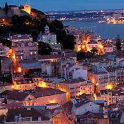 View of Lisbon's São Jorge Castle and river by dusk