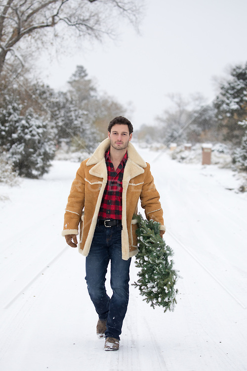 hot man walking in snow with a Christmas Wreath