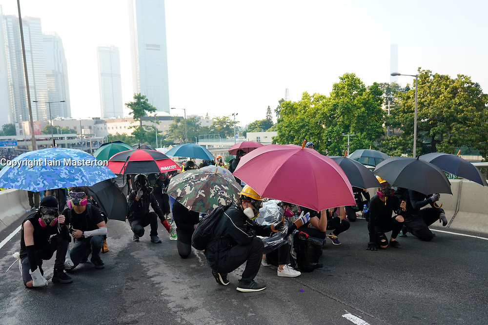 Hong Kong. 1 October 2019. After a peaceful march through Hong Kong Island by an estimated 100,000 pro democracy supporters, violent flared up at Tamar, Admiralty and moved through Wanchai district. Police used teargas and baton rounds and water cannon. Hard core group lit fires, threw bricks and Molotov cocktails at police. Violence continues into evening.  Protestors shelter from police fire using umbrellas. Iain Masterton/Alamy Live News.