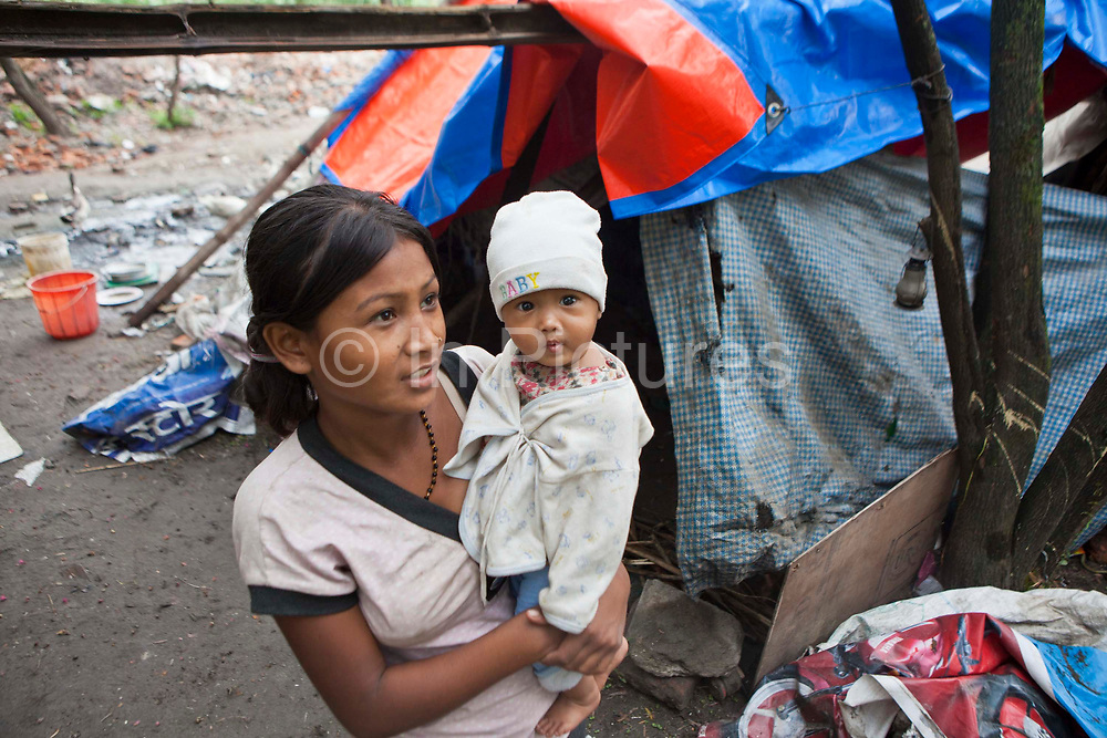 A young Nepalese mother holds her baby in her arms outside their plastic tent home in United Nations Park, a slum in Paurakhi Basti, next to the Bagmati River in the centre of Kathmandu, Nepal.  The slum was recently demolished by the Nepalese government, however a few shacks have been rebuilt and many people continue to live on this site.