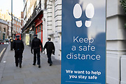Three Met Police officers walk down the street near Covent Garden, past a signpost urging the public to maintain the correct Social Distances at the end of Lockdown 2 during the second wave of the Coronavirus pandemic, on 1st December 2020, in London, England.