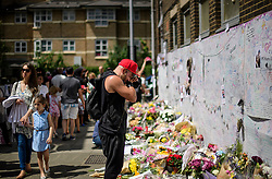 © Licensed to London News Pictures. 17/06/2017. London, UK. An emotional man looks at floral tributes left for the victims of Grenfell tower block in west London following a devastating fire earlier this week. The blaze engulfed the 27-storey building killing 12 - with 34 people still in hospital, 18 of whom are in critical condition. The fire brigade say that they don't expect to find anyone else alive. Photo credit: Ben Cawthra/LNP