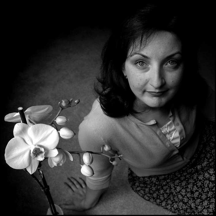Melinda Wallace sits on the carpet near a blooming orchid in her San Francisco apartment on July 11, 2006. Wallace has suffered from depression for most of her life and has attempted suicide...Wallace was one of thousands of Bay Area Residents who participated in the American Foundation for Suicide Prevention annual fundraising walk, Out of the Darkness, in San Francisco, CA on July 22, 2006...Photo by Erin Lubin.
