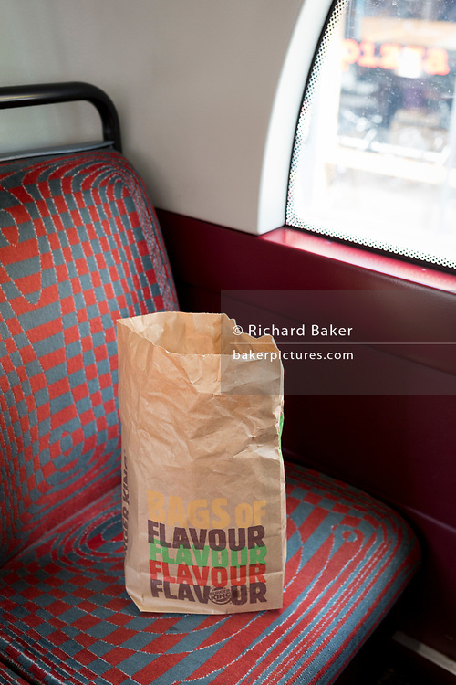 A brown paper bag containing the remnants of fast food from Burger King discarded on a seat in a London bus, on 30th April 2019, in London, England