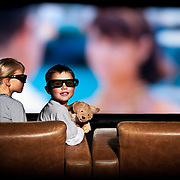Two children watch a 3D television screen in a cinema room.