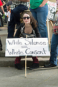 Young woman protestor holds sign at 2015 May Day Rally in Portland, Oregon titled White Silence White Consent