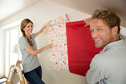 Married couple decorating new home wallpaper