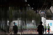 A construction worker, in silhouette, walks under a part of the new national stadium construction site in Gaiemmae,,Tokyo, Japan. Monday April 22nd 2019