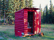 Bright red outhouse at the home of Donna and Larry Gondek, Chistochina, Alaska.