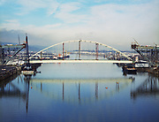 Ackroyd C03408-3. the Fremont Bridge steel arch span being lifted into position. March 16, 1973.