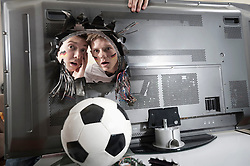 Two shocked teenage boys looking at soccer ball demolishing TV