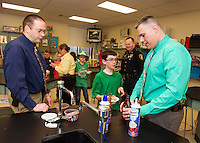 Sgt. Det. Chris Jacques and Chief Tony Bean Burpee help Patrick Gandini top off his ice cream sundae with sprinkles, chocolate sauce and whipped cream during the D.A.R.E. ice cream party at Gilford Middle School Thursday morning. (Karen Bobotas/for the Laconia Daily Sun)