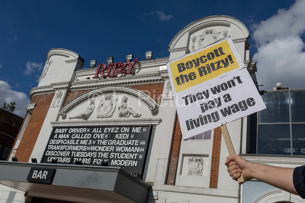 A placard is held up to the frontage of the Ritzy Cinema, part of the Picturehouse chain, in dispute with Bectu union employees for a living London wage, on 3rd July 2017, in Brixton, London, England. The Picturehouse chain is owned by Cineworld which has 2,000 cinema screens in nine countries. The London Living Wage is set at £9.75 per hour the national rate is £8.45.