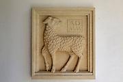Millennium sculpture Sebastian Brooke carved relief of lamb in porch of Saint John the Baptist church, Mildenhall, Wiltshire, England, UK