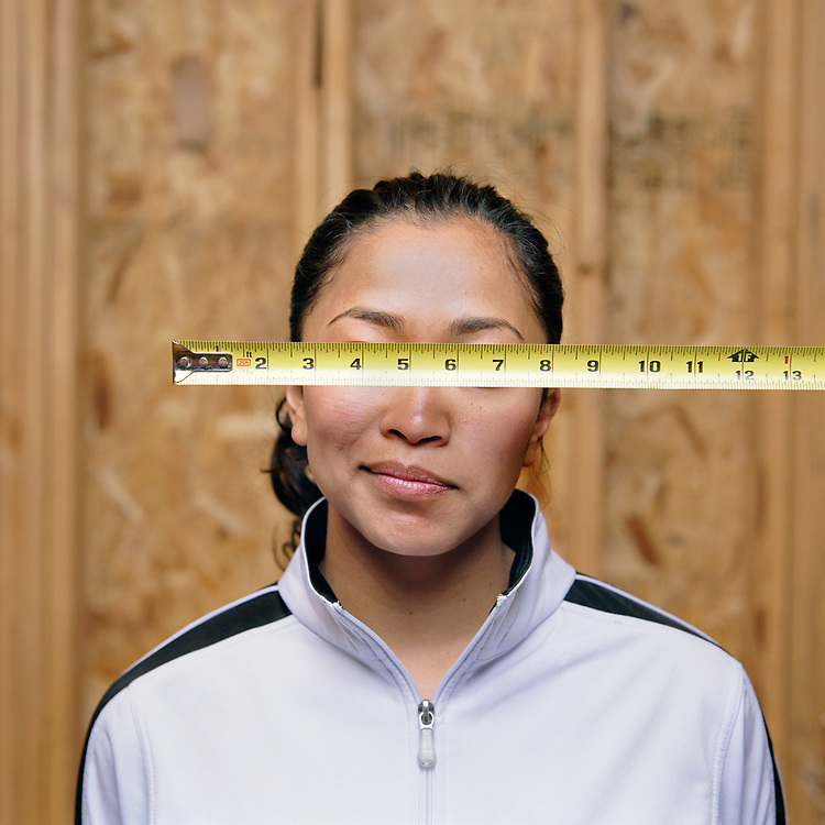 Woman in a construction site with a tape measure in front of eyes.