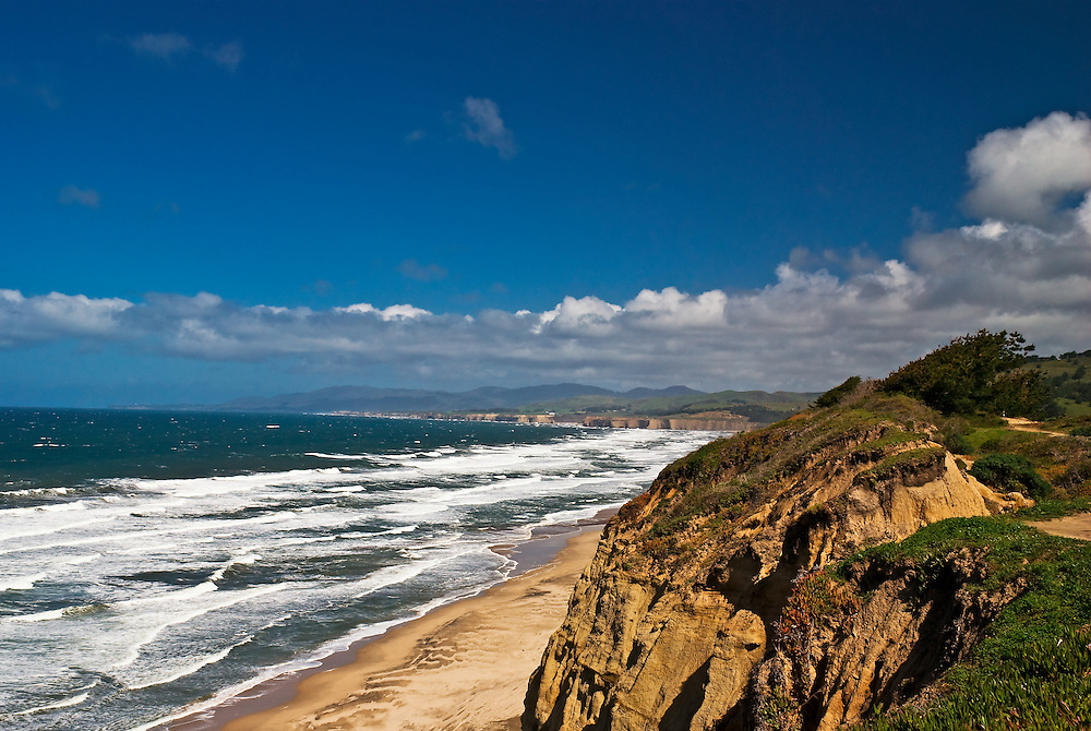 SUBJECT: California Coast. IMAGE: Several miles of steep bluffs run up the Californian coast with surf on San Gregorio State Beach and the Santa Cruz mountains inland
