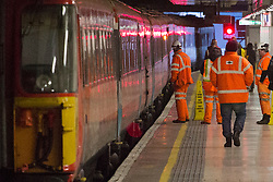 © licensed to London News Pictures. London, UK 17/01/2013. Rail workers trying to solve the technical problems after a Gatwick Express train catches fire in Victoria Station during the rush hour and causing the station closure. Photo credit: Tolga Akmen/LNP