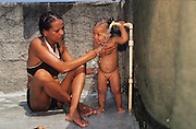 WATER. Rocinha Favela, Rio de Janeiro, Brazil, South America. Young baby child with outside water tap. Although Rocinha is technically classified as a neighborhood, many still refer to it as a favela. It developed from a shanty town into an urbanized slum. Today, almost all the houses in Rocinha are made from concrete and brick. Some buildings are three and four stories tall and almost all houses have basic sanitation, plumbing, and electricity. Compared to simple shanty towns or slums, Rocinha has a better developed infrastructure and hundreds of businesses. There is also lots of deliquency, crime and drugs in the favelas.
