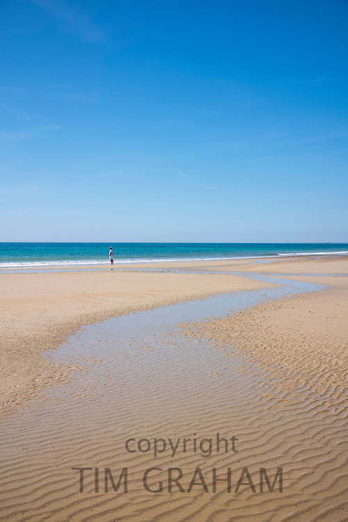 Lone figure of holidaymaker on sandy beach with ripples in the sand - Les Laveurs Beach, St Ouen, west coast of Jersey, Channel Isles