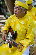 Portrait of a vietnamese man playing guitar in Ao Dai (traditional outfit). Tao Dan Park, Ho Chi Minh city, Vietnam, Southeast Asia