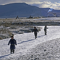 MONGOLIA, Darhad Valley. Nomadic children play on frozen stream in canyon, as their families gradually migrate up into forested hills for the winter.
