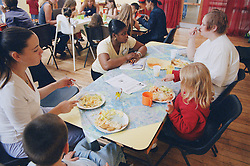 Group of mothers and children eating and talking to nursery nurse at women's shelter,