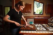 USA, Oregon, Eugene, young woman slicing figs for salad. MR
