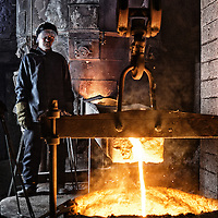 Portrait of the iron foundry Furnaceman next to molten crucible of iron  in old industrial setting