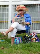 © Licensed to London News Pictures. 01/06/2012. Epsom , UK A woman   sips wine whilst reading a paper.  Ladies Day today 1st June 2012 at Epsom 2012 Investic Derby Festival. The Queen will attend tomorrow's race meet as part of the 60th Jubilee celebrations. Photo credit : Stephen Simpson/LNP