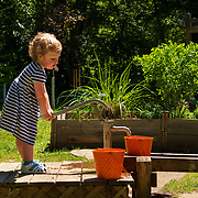 Edith Stradtman pumps water into a bucket to water plants at the ArcelorMittal Children's Garden at the Friendship Botanic Gardens in Michigan City, Indiana. Nathan Lambrecht/Journal Communications