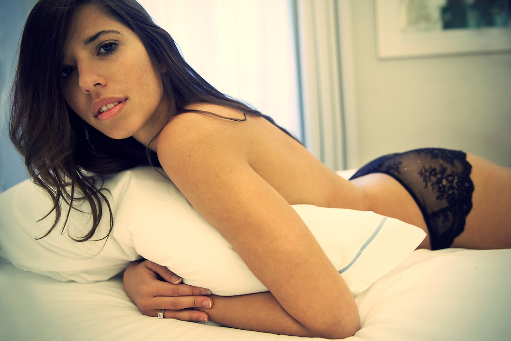 Sexy woman in lingerie lying on bed.