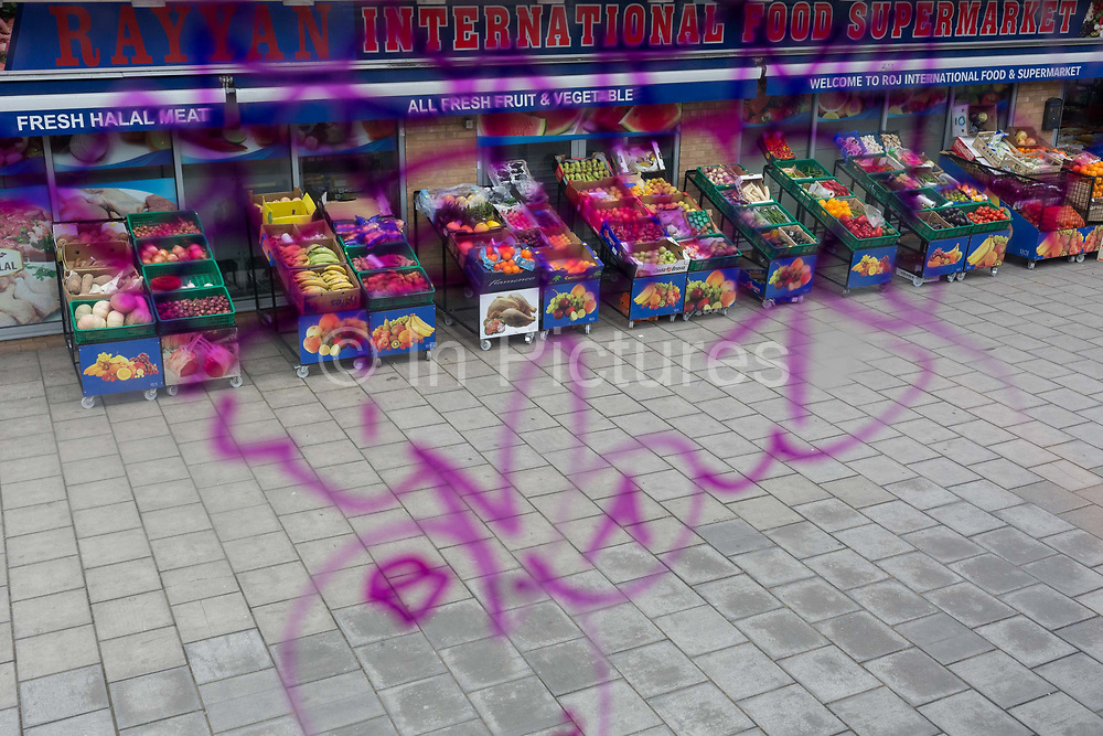 Seen through the purple swirls of graffiti marking the window of a bus driving through south London, a fruit and veg retailer on the Old Kent Road, on 21st March 2019, in London, England.