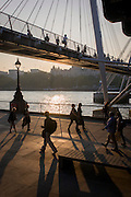 Silhouettes of commuters crossing Hungerford Bridge and of walkers on Thames riverbank.