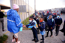 South Africa - Cape Town - 24 - August - 2020 Neighborhood Watch Thozama Mfube saniters kids at  Mangaliso Primary School as  pupils being screened as they return back to School today Photographer Ayanda Ndamane African News Agency(ANA)